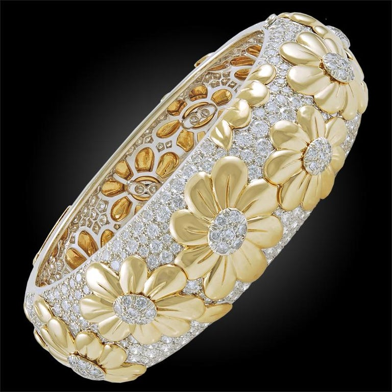 A remarkable duo comprising a 1970's 18k white and yellow gold flower motif bangle with matching earrings, set with an opulence of luminous brilliant-cut diamonds throughout, diamonds weighing approximately 20 carats. Signed Van Cleef & Arpels,