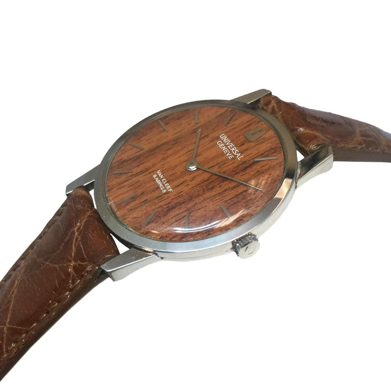 Circa 1970s Universal Geneve Retailed by Van Cleef & Arpels Rare Wood Dial Wrist Watch, 31 MM Diameter 3 piece Stainless Steel Case, 6 MM thick. 17 Jewel Mechanical, manual wind movement.   Fitted with a Wood Dial and having raised Markers. Hadley