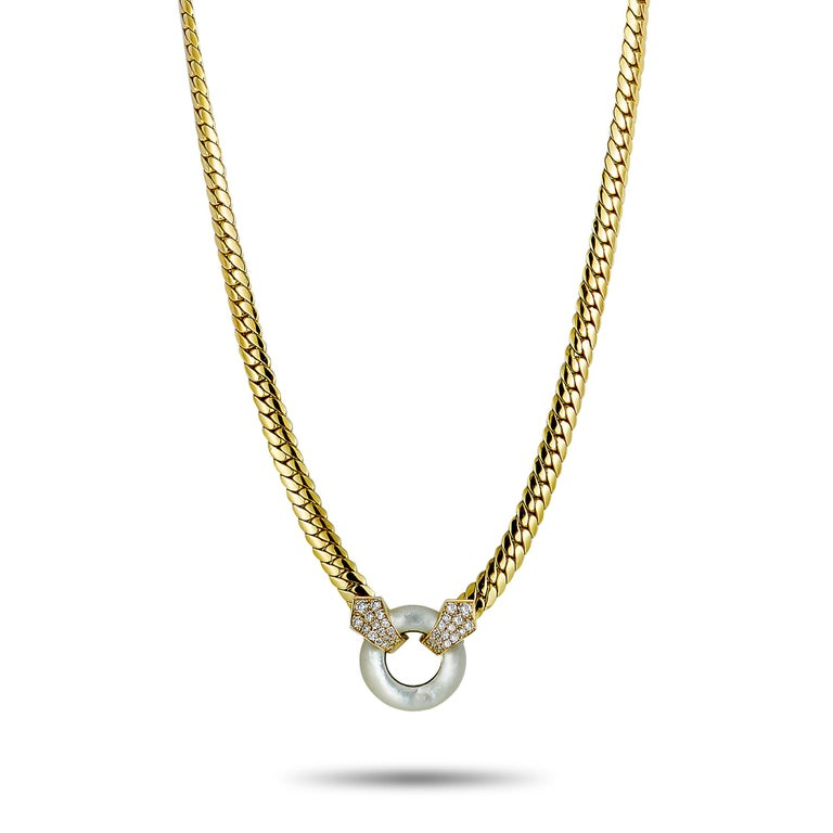 """This vintage Van Cleef & Arpels necklace is made of 18K yellow gold and weighs 44.2 grams. It is set with mother of pearl and a total of 0.75 carats of diamonds that feature grade F color and VVS clarity. The chain is 15.00"""" long and the pendant"""