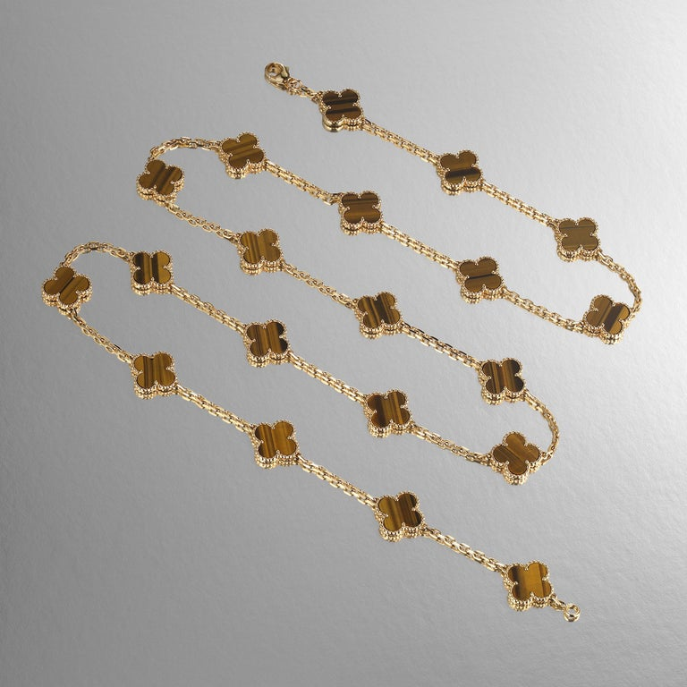Classic Van Cleef & Arpels Vintage Alhambra long-version necklace featuring 20 Tiger's Eye clover motifs and set in 18 karat yellow gold. Created in 1968 and taking design cues from traditional Moorish architecture, the Vintage Alhambra creations by