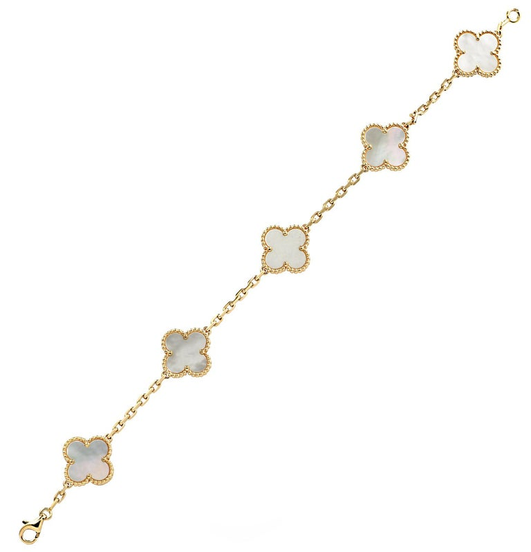 From the House of Van Cleef & Arpels, this exquisite Vintage Alhambra bracelet, 5 motifs, finely handmade in 18 Karat yellow Gold, featuring a symmetrical design inspired by the clover leaf. The clovers are embellished in mother of pearl and are
