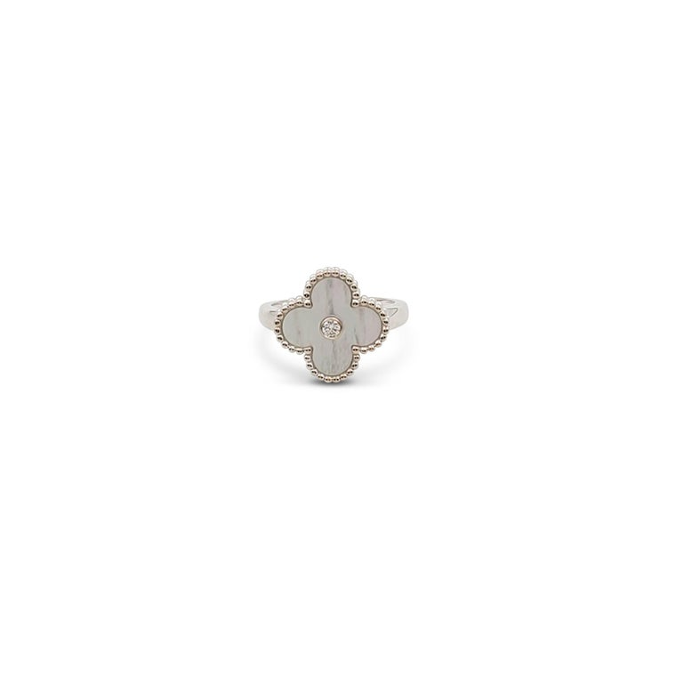 Authentic Van Cleef & Arpels 'Vintage Alhambra' ring crafted in 18 karat white gold centers on a clover motif in mother-of-pearl set with a round brilliant cut diamond center weighing an estimated 0.06 carats (E-F color, VS clarity). Signed VCA,