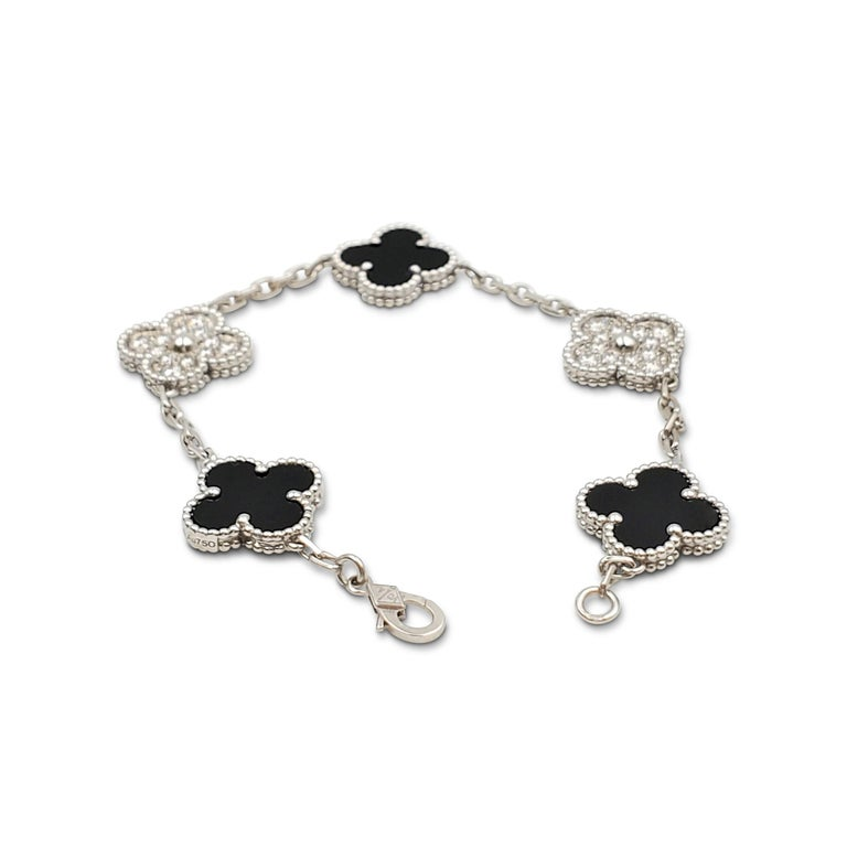 Authentic Van Cleef & Arpels 'Vintage Alhambra' bracelet crafted in 18 karat white gold features alternating clover motifs of onyx and pave diamonds (E-F color, VS clarity) weighing an estimated 0.72 carats total weight. The bracelet measures 6 1/2