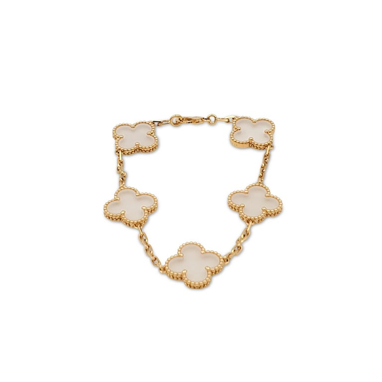 Authentic Van Cleef & Arpels 'Vintage Alhambra' bracelet crafted in 18 karat yellow gold features clover motifs of rock crystal. The bracelet measures 6 1/2 inches in length and is signed VCA, Au750, with serial number and hallmarks. The bracelet is