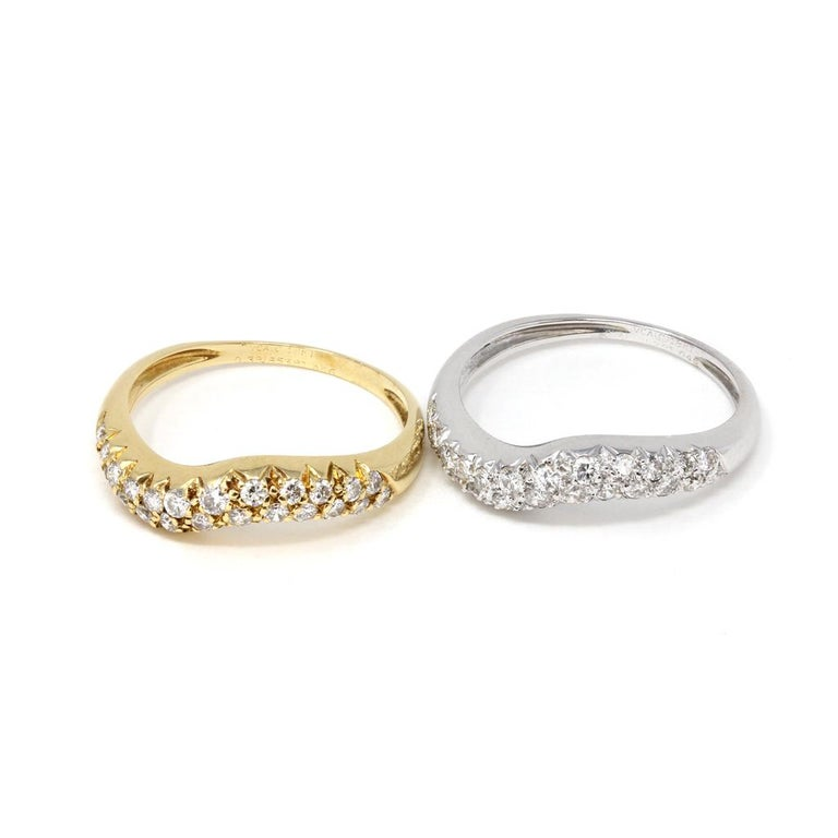 A set of two tone diamond bands by the French house of jewelry Van Cleef and Arpels. The rings and designed on top In a wavy fashion with pavé set diamonds G color and VS-VVS Clarity. One band is 18k white gold and the other is 18k yellow gold. The