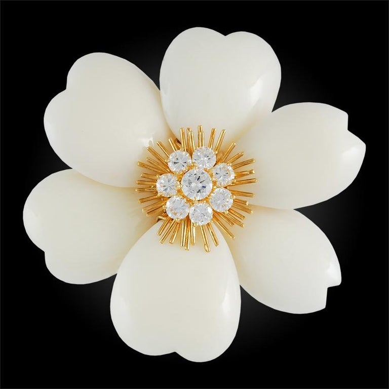 A rare Van Cleef & Arpels 'Rose de Noël' brooch set in 18k yellow gold, each piece designed as a flower head, set in the center with brilliant-cut diamonds on spiked gold filaments, and surrounded by petals of finely carved white coral