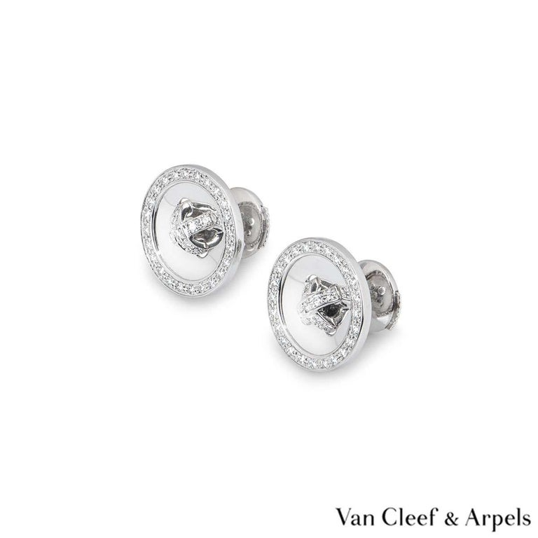 A pair of 18 carat white gold diamond earrings by Van Cleef & Arpels. The button motif earrings are set with round brilliant cut diamonds in the centre and around the outer edge. There are 66 diamonds with a total weight of approximately 0.39