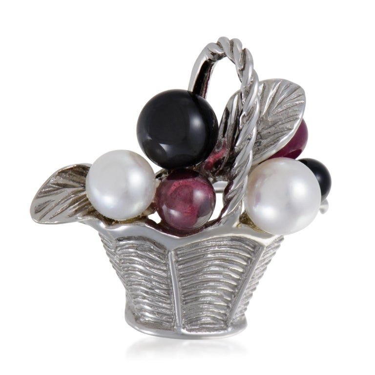 Ideally spherical and tastefully combined, the charming pink tourmalines, stunning onyx stones and delightful pearls are placed in an intricately textured basket of 18K white gold in this adorable brooch from Van Cleef & Arpels.