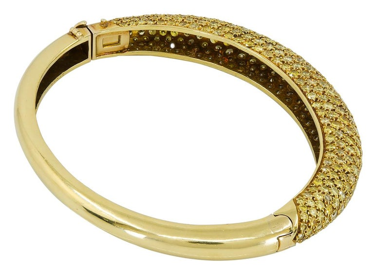 VAN CLEEF & ARPELS Yellow Diamond Bangle Bracelet in 18k Yellow Gold.  A classic hinge bracelet by Van Cleef & Arpels dating from the 1970s, designed as a thin bombé-shaped bangle. The top half of the piece features a nine-rows of scattered fancy