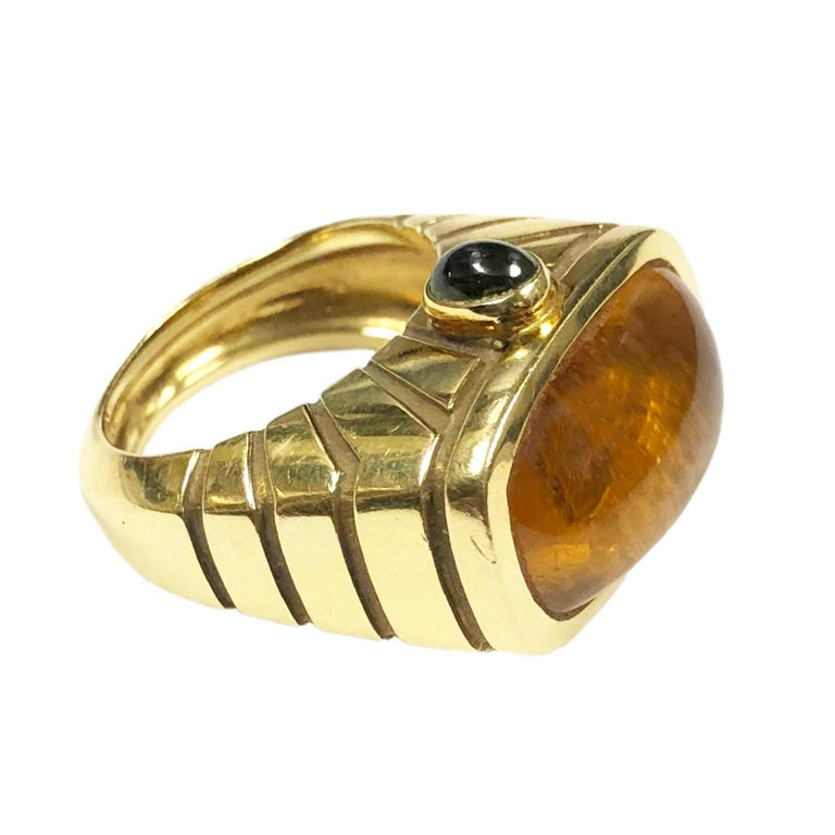 Circa 1980s Van Cleef & Arpels 18K Yellow Gold Ring, having nice think and heavy gold construction and centrally set with Domed Cabochon Topaz measuring 15 X 9 MM approximately 5 - 6 Carats. Further set on each side with a Cabochon Peridot. The ring