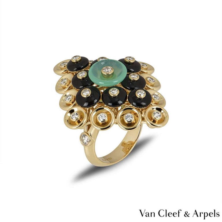 A unique dress ring from the Bouton d'or collection by Van Cleef & Arpels. The ring features a paillette design which includes diamonds, onyx and chrysoprase. The are a total of 23 diamonds totalling 0.68ct. The ring measures 2.8cm in width and