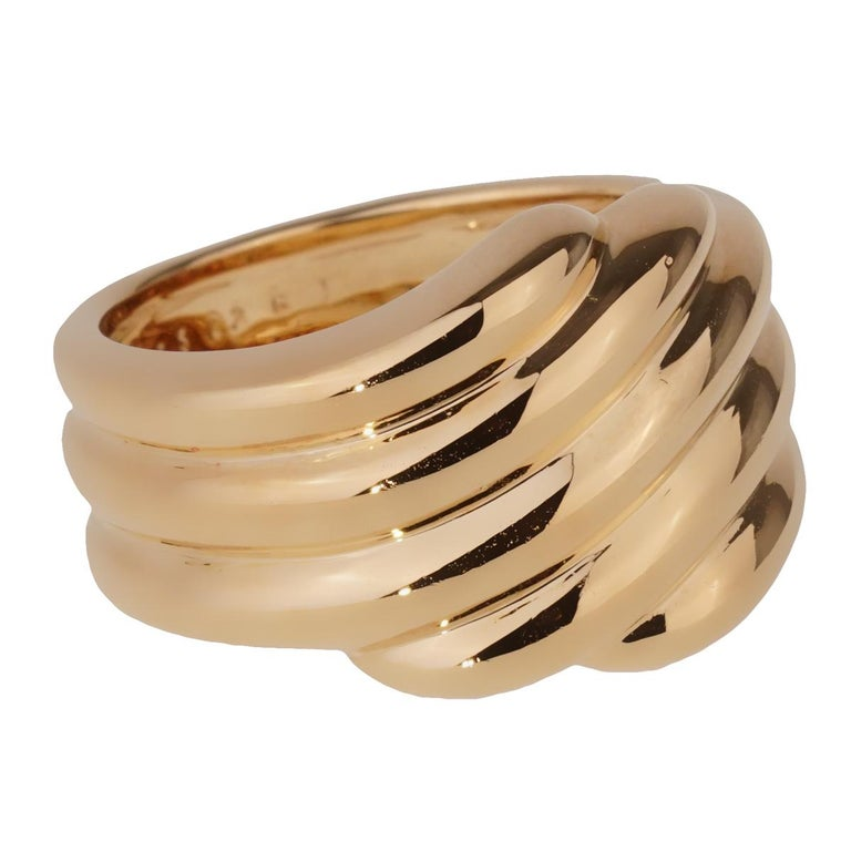 A chic Van Cleef & Arpels cocktail ring featuring a ribbed pattern in 18k yellow gold.  Size 3 3/4 Resizeable