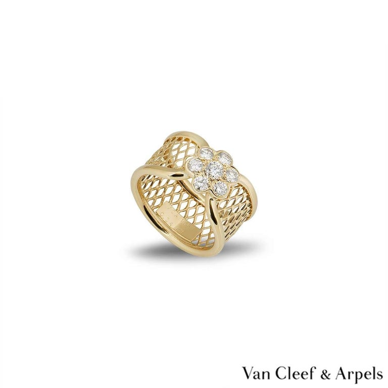 A beautiful 18k yellow gold ring from the Fleurette collection by Van Cleef & Arpels. The mesh design ring has a diamond set flower motif in the centre. There are 7 round brilliant cut diamonds totalling 0.34ct. The ring measures 1cm in width and is