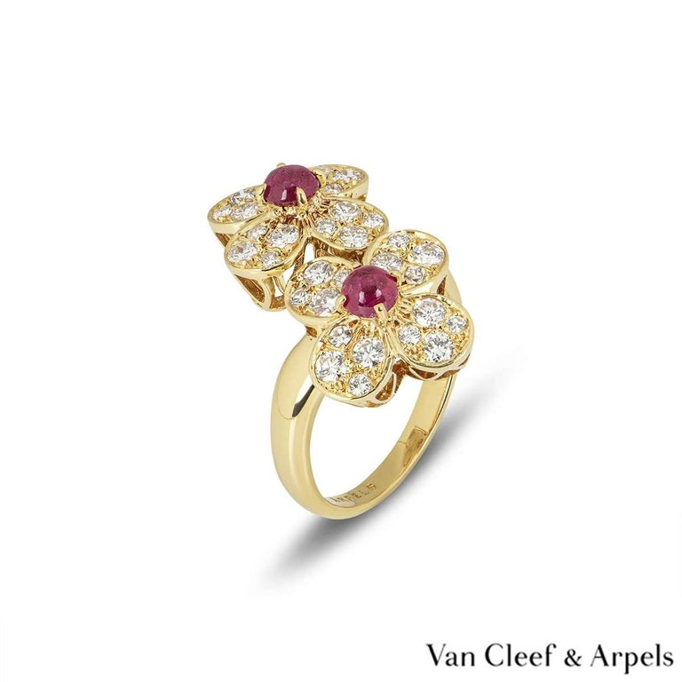 A beautiful 18k yellow gold Van Cleef & Arpels ring from the Trefle collection. The ring comprises of two flower motifs, with a cabochon cut ruby in the centre. Complementing the rubies are round brilliant cut diamond set petals totalling