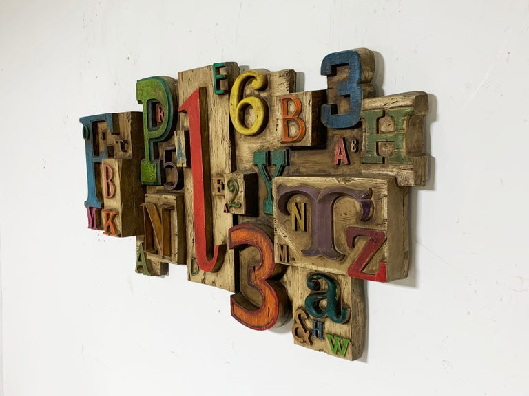 Wall sculpture by Vanguard Studios, dated 1969, composing letters and numbers in a vareity of fonts and sizes, assembled in a multi-dimensional arrangement.