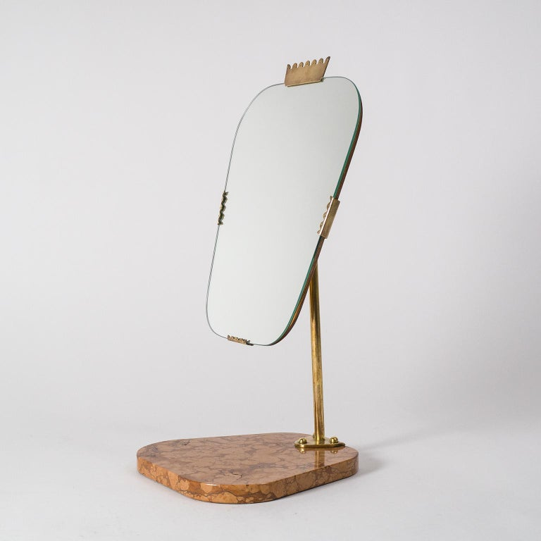 Beautiful Swedish vanity mirror, late Art Deco, circa 1940. Solid red stone base with a brass arm and pivoting mechanism holds a tapered mirror with teak backplate and brass details. Very nice condition with patina on the brass. Mirror measures: