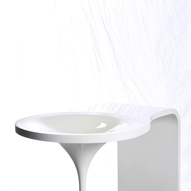 Inspired by melting snow and icicles, this small vanity table easily fits into the corner of most bedrooms. The shiny table surface incorporates a bowl for holding cosmetics. It can also function as an entry table holding water for flowers, keys, or