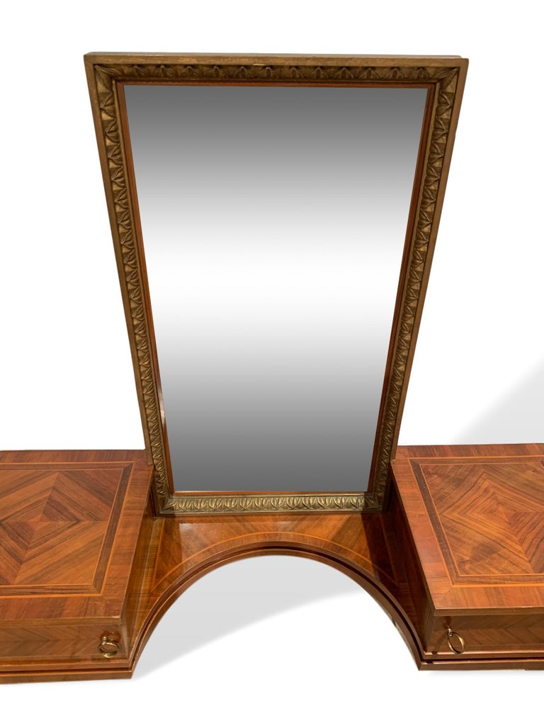 Vanity with attached gilt mirror, inlaid with exotic woods, Italian, circa 1900. The vanity is parquetry-inlaid, consisting of kingwood, satinwood, walnut and other exotic timbers, in geometrical patterns to top and chevrons to the doors and sides,
