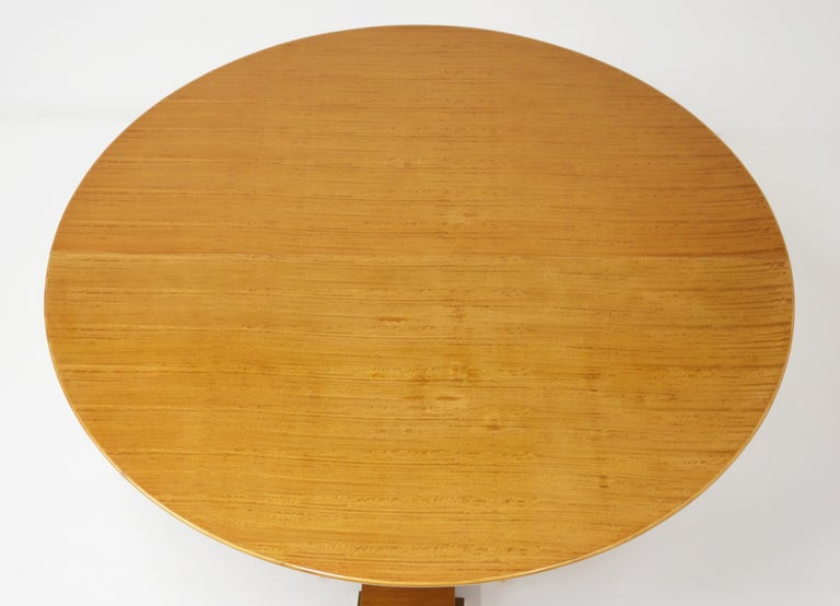 Varnished Lemon-tree circular table by Jean Royère, circa 1950. The wing-shaped circular top stands on a central foot composed of three spindle-shaped columns. Each column is set with a circular gilt bronze ring. The table stands on a base set off