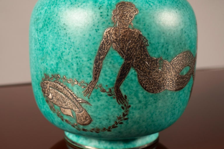 Stoneware vase with an evergreen glaze and silver detail of a mermaid with fish. Silver provided by ARGENTA.