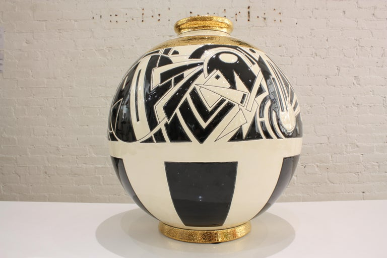 Superb round vase in limited edition in Art Deco style. The artist Nicolas Blandin was commissioned by Les Emaux de Longwy to create this graphic design for their world famous Boule vases. Black and ivory tones highlighted by crackled gold leaf give