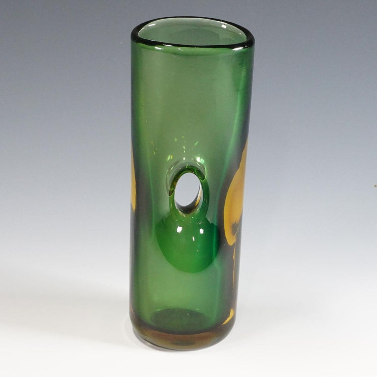 A forato vase in green, and amber colored glass designed by Fulvio Bianconi in 1951, manufactured by Venini, Venice circa 1950s. With etched signature 'venini murano italia' on the base. Traces of use on the base, thus the signature is almost not
