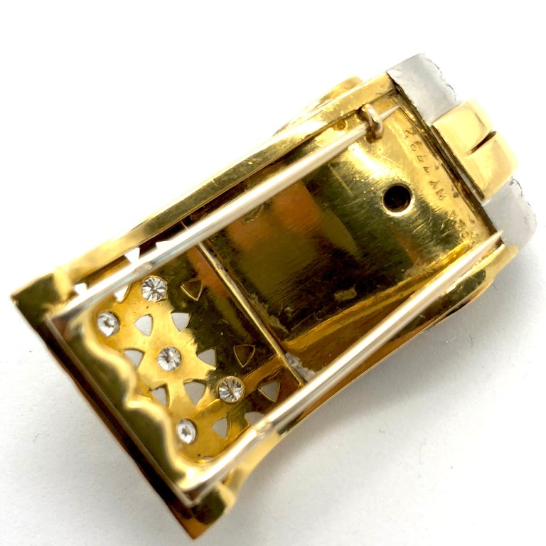 A ruby and diamond 18k yellow gold clip by VCA from the retro period, 1950s. It has fine round brilliant solitaire diamonds, weighing approximately 3 carats, and ruby carrés. The clip has an iconic ludo design and is marked VC&A NY and numbered