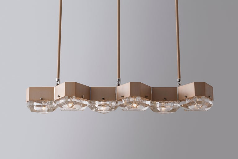 Vega chandelier is a modular lighting system fabricated from geometric metal components that support cast glass diffusers. Arranged in a linear form with a gold anodized body, polished nickel accents and cast glass diffusers. Lamping is shown in