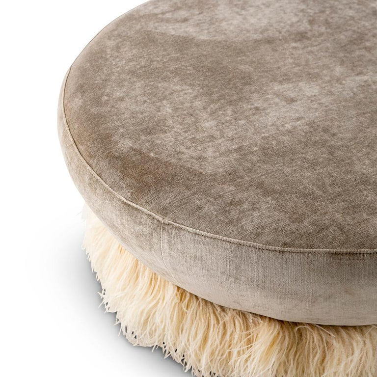 This ottoman is part of the Ostrich Fluff collection designed by Egg Designs and manufactured in South Africa. The velvet ottoman is finished off with a colored, delicate, genuine ostrich feather skirt trim.
