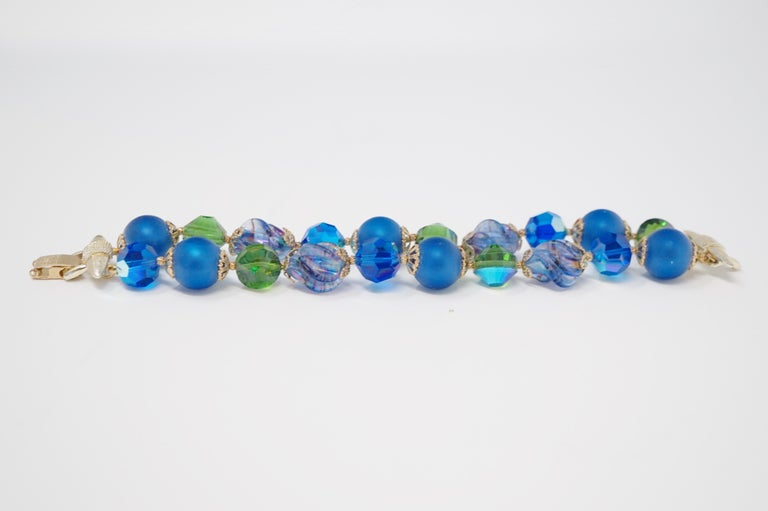 This exquisite double strand beaded bracelet by Vendome features a mix of matte cobalt blue beads, mercury glass beads and Aurora Borealis iridescent crystal beads with gold tone accents. Signed Vendome on gold tone clasp.    Operated as a