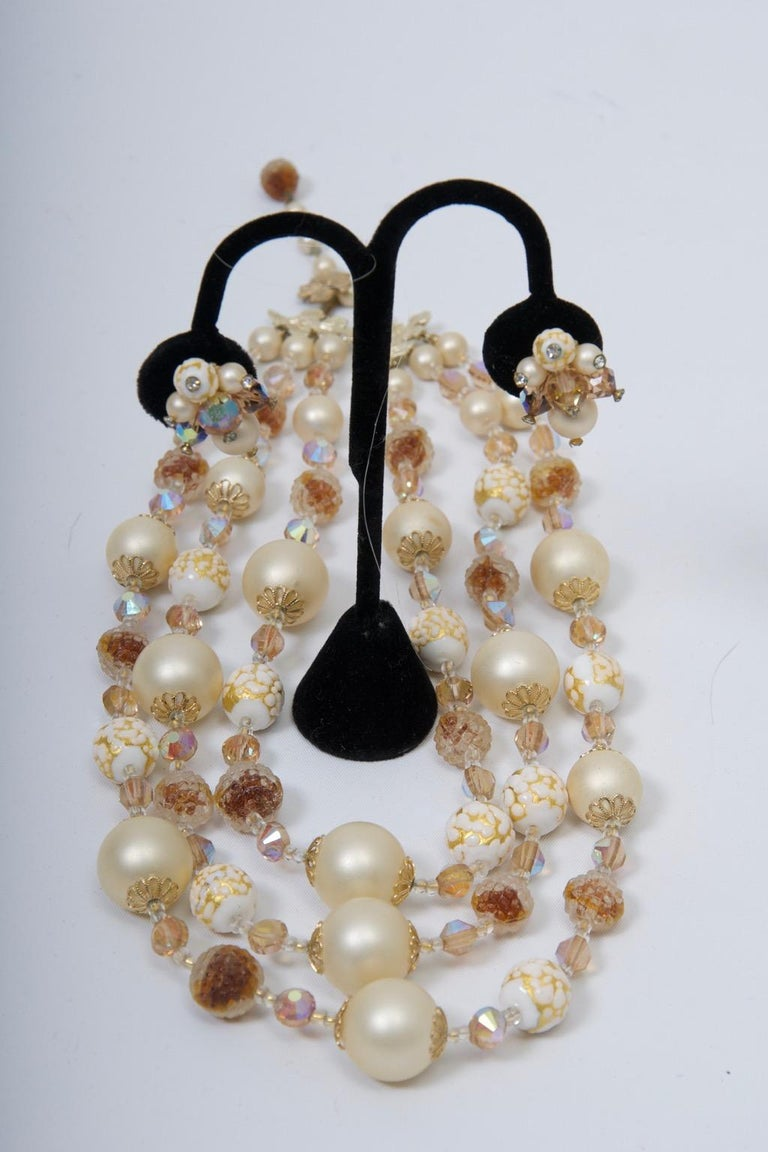 Vintage Vendome set composed of a three-strand necklace and earclips featuring large faux pearls interspersed with faceted topaz-toned and iridescent crystals and white beads with gold swirls. Adjustable clasp. Earrings with representative beads