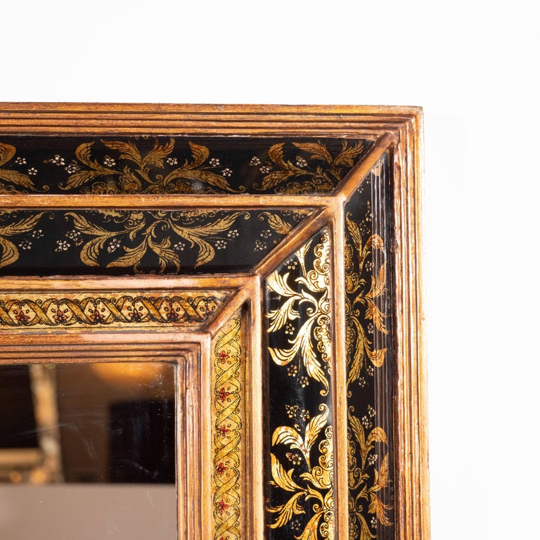 This refined mirror was realized in Venice, Italy, circa 1945. It features a segmented giltwood frame with a raised pyramidal border in relief with reverse églomisé gold foliate and floral detailing on both sides. The interior border framing the