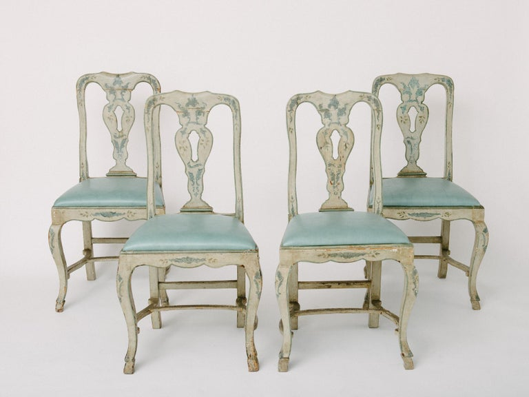 18th century blue-gray painted Venetian side chairs with leather seats. Chairs have a Heraldic style cross maker's mark engraved on backs of chairs. Features hand carved stretchers and pied-de-biche hooves, seat covered in a sky blue leather. Uneven