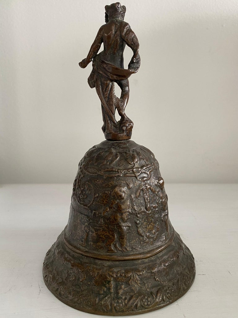 This bronze bell is of the type cast in Venice in the 16th century. It is topped with a figure of Mercury surmounting a procession of putti with garlands and a blank cartouche. It measures 7