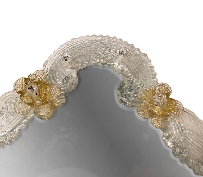 A Venetian mirror with applied amber glass flower decoration, circa 1950s.  Measurements: Height 17