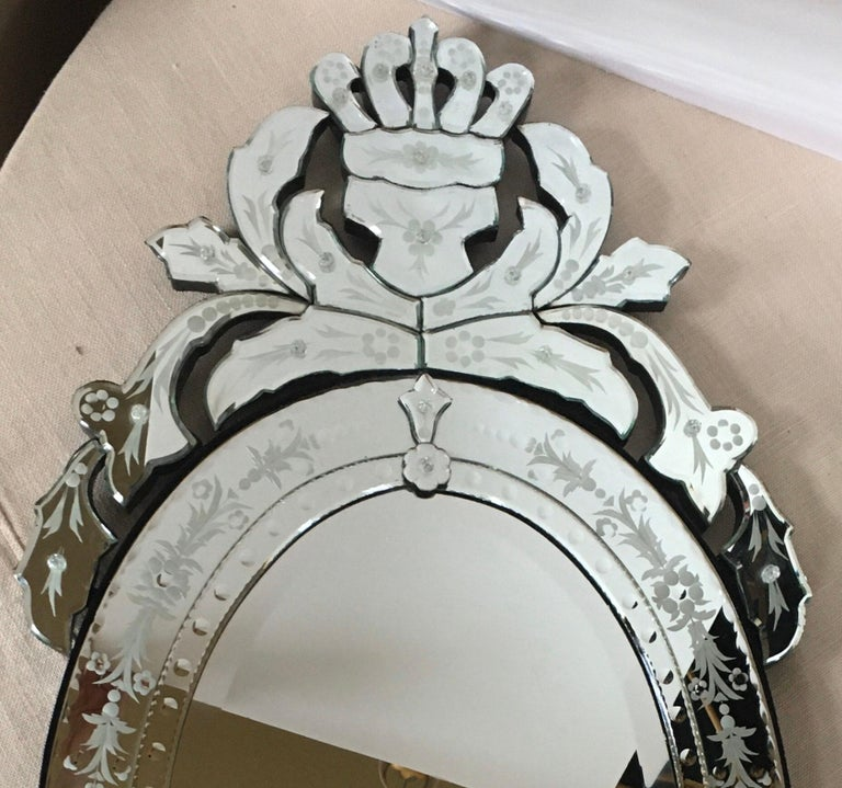 Large oval Venetian Hollywood Regency style decorative wall mirror with beveled and scalloped detailing. This elegant mirror features superbly etched floral motifs and beveled edges with a contoured crown-like crest and a large leaf-shaped pediment