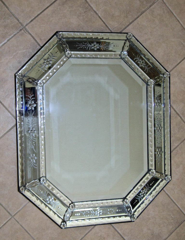Very attractive 1940s octagonal Venetian Italian etched wall mirror. The mirror is expertly handcrafted revealing numerous intricate etched flower and scroll motif threw out. The large inner mirror is beveled, the outer panels have lots of finely
