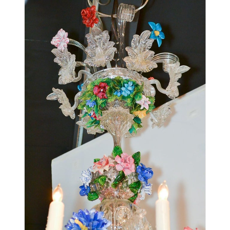 Magnificent early 20th century Venetian multi-color glass chandelier in hues of green, blue, lavender, red, and pink. The ornately designed crown with leaf scrolls and leaf sprays adorned with shoots of colorful wildflowers. The shaped stem banded