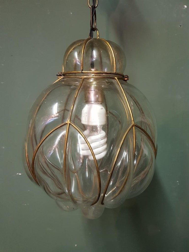 Beautiful model of an old Venetian Murano hanging lamp made of clear glass blown into a metal frame and surrounded by air bubbles in the glass. It is further in good condition with new wire and fitting. Originating from the mid-20th century.