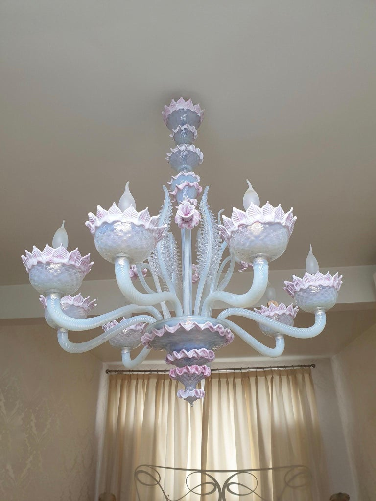 Venetian blown glass chandelier, crafted in Murano Italy, in the mid-20th century. A timeless Murano circular chandelier with an elegant structure finely decorated with eight curved arms ending with upwards corolla shaped bobeiges. A central pillar