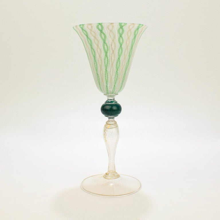 A wonderful large Venetian glass wine goblet with green, white, and gold latticinio swirl decoration. 