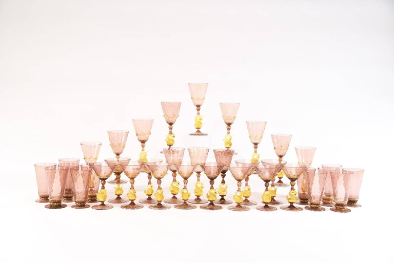 This is a complete hand blown Venetian stemware service made by Salviati, circa 1920s. The 36 piece set consists of 12 each of water goblets, wine goblets and champagne coupes, each one featuring a figural golden yellow swan connector and applied