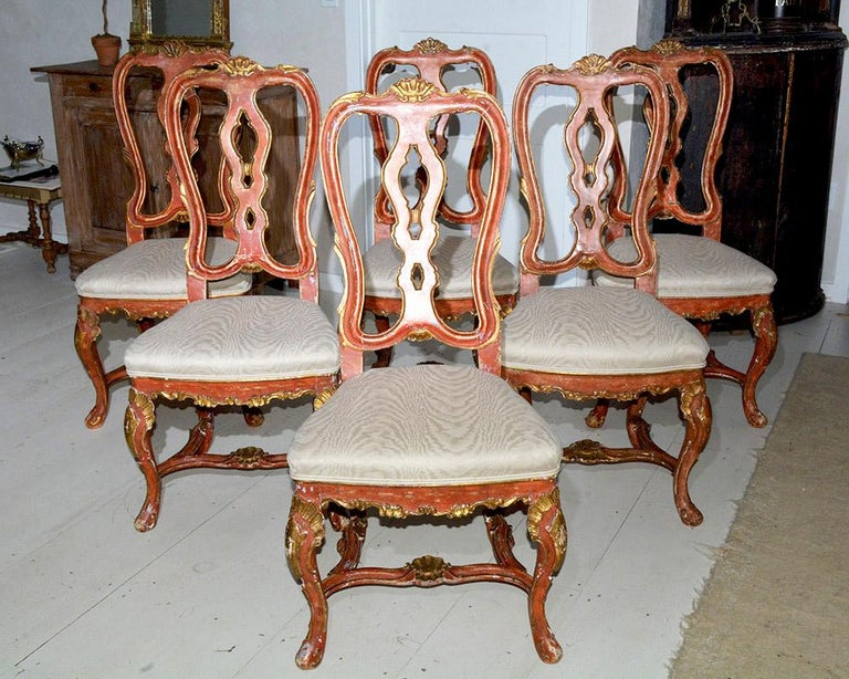 Very special set of 6 Italian Baroque or Swedish Rococo style dining side chairs featuring tall shapely backs, stretcher base, Queen Anne style legs, solid wood construction. Hand painted red and gilded with a distressed finish that accentuates the