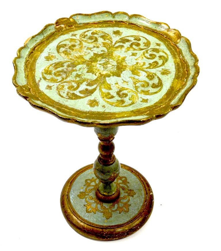 Very decorative carved wood table in faded blue and gilt finish, finish shows wear, normal and consistent with age. Circular top on turned wood base. Marked on bottom Made in Italy, circa 20th century, probably Florentine Furniture Company