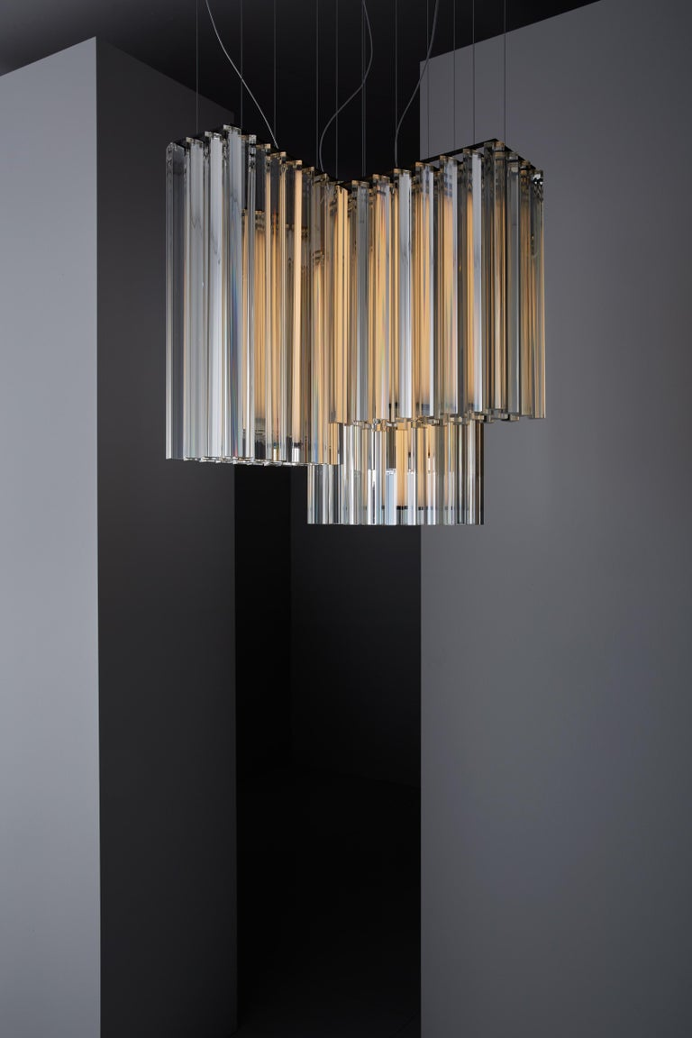 Suspended lamp with diffused light. Black metal structure with steel cables, composed of crystal triangular trihedrons. Strip LED inside the central cylindrical body.   Location: Interior Light Source: 1×12W LED 1590lm 2700°K CRI90 + 2×17W LED