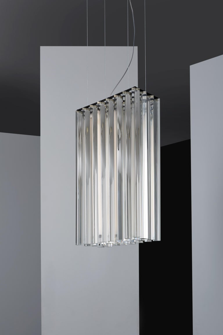 Suspended lamp with diffused light. Black metal structure with steel cables, composed of crystal triangular trihedrons. Strip LED inside the central cylindrical body.   Location: Interior Light source: 1 × 17W LED 2225lm 2700°K CRI90 Voltage:
