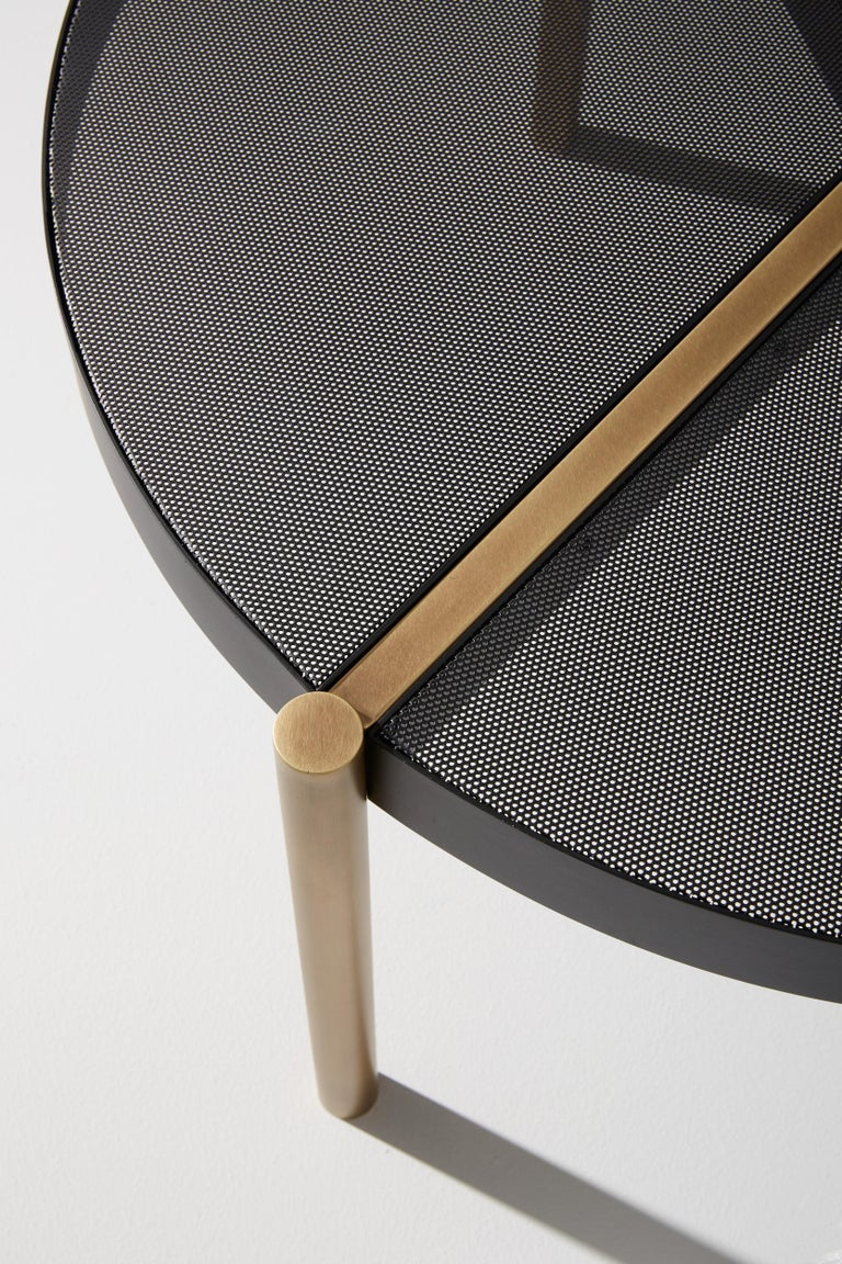 Coffee table composed of light burnished brass structure and matte black perforated metal top.