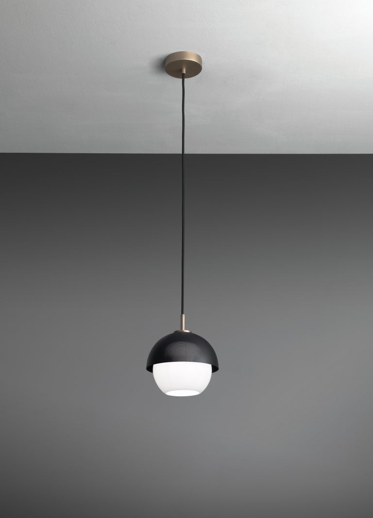 Suspended lamp with diffused light. Light burnished brass structure with matte gold or matte black perforated metal lampshade. White Murano blown glass diffuser. Specifications: Function: Suspension Location: Interior Light emission: Diffused