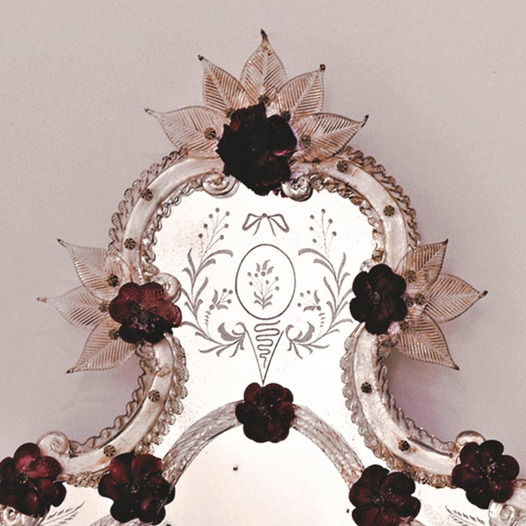 This delightful reproduction of an antique mirror features a sinuous profile with three-dimensional rose and flower inserts made of prized, coral-toned glass paste that confer a delicate, feminine charm. Floral details are both engraved on the