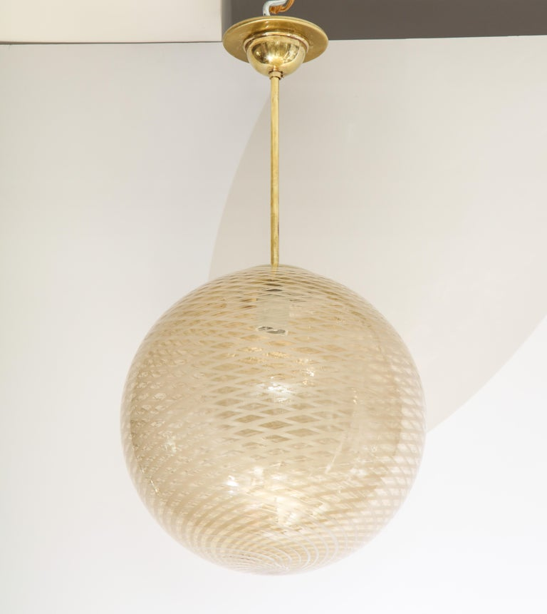 Venini early and rare 1930s stunning reticello glass globe chandelier in a beautiful and warm gold, cream and white hand blown glass; iconic swirl design with brass columnar support and canopy. All original. (Re-wired for USA standards). Attributed